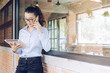 Portrait of young mixed race businesswoman (Her dad is British, Her mom is Thailand) speaking on her mobile phone and looking something on her tablet.
