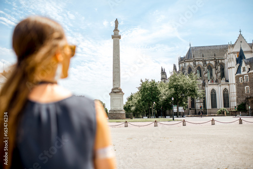 Foto Murales Young woman enjoying view on the Louis column and saint Pierre cathedral in Nantes city in France