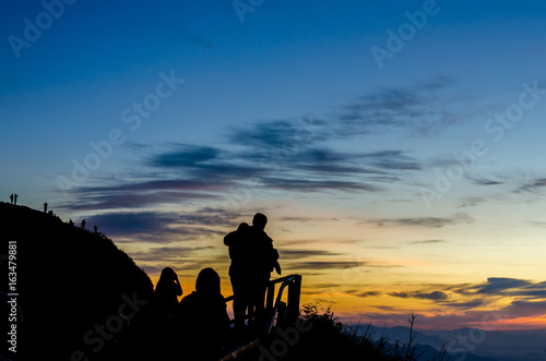 Silhouette of woman standing on the mountain against vivid sunset sky,located phu chi dao ,thailand.