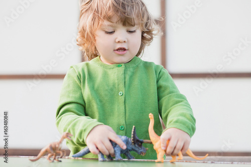 Plagát toddler kid playing with a toy dinosaur