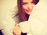 Smiling woman holding cup of drink in bed - 163485074