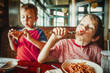 Leinwandbild Motiv kids eat pizza and pasta at cafe. children eating unhealthy food indoors