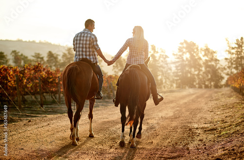 Smiling couple holding hands while riding through an autumn vineyard