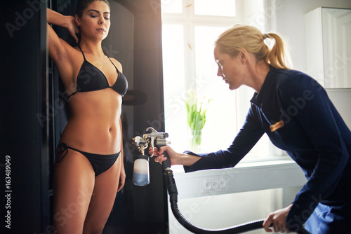 Woman spraying client with aerograph during spraytan session Poster