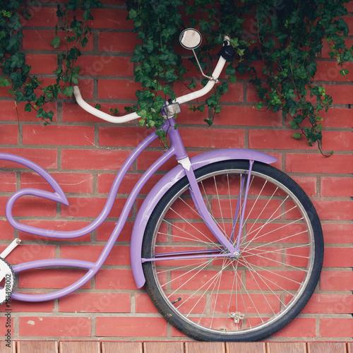 Aluminium Fiets A lilac vintage bicycle hangs on a brick wall. Decor concept.