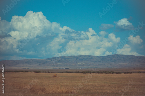 Blue sky with clouds. Summer steppe landscape. African desert with mountains view.
