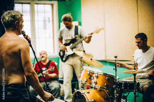 Staande foto Muziekwinkel Behind scene. Rock band practice in messy recording music studio