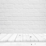 Empty wood table with white brick wall texture.