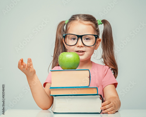 beautiful cute little girl counting on fingers behind the books