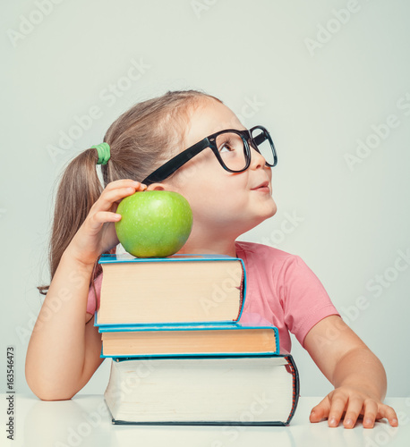 beautiful cute little girl with books and green apple smiling and looking up