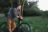 Handsome Young Man Cyclist Standing Resting With Bicycle Near Tree In Summer Park And Resting Recreation Travel Destination Concept - 163546803