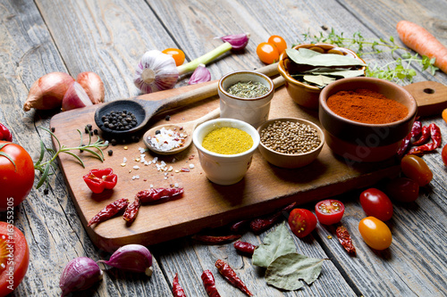 Spices and vegetables on wooden board