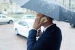 Broker under umbrella phoning in the street - 163562282