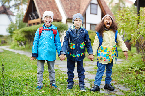 Three happy little schoolkids with backpacks, one of them African, standing holding hands outdoors and laughing on sunny autumn day