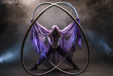 Fairy-tale character assassin in a purple cloak with a hood with two large cyr wheel hoops - 163566212