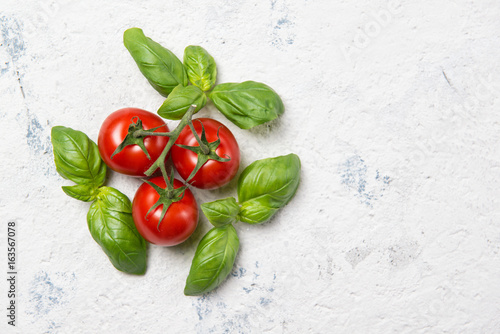 Fresh cherry tomatoes with basil leaves on a stone table, top view with copy space