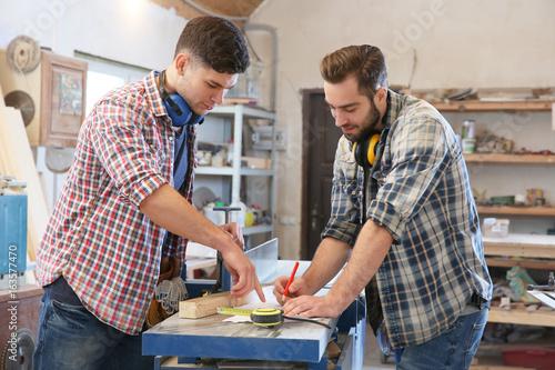 Deurstickers Carpenters applying marking onto drawing in workshop