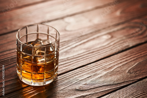 Glass of whiskey with ice cubes on wooden table