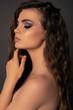 beautiful girl with dark hair and evening makeup posing at studio