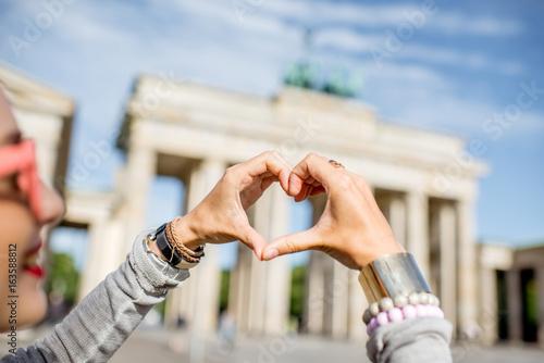 Fotobehang Berlijn Young woman tourist making heart shape with hands in front of the famous Brandenburg gates in Berlin