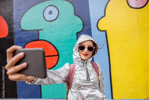 Spoed canvasdoek 2cm dik Graffiti Young woman tourist making selfie photo standing in front of the Berlin wall in Germany
