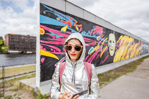 Aluminium Graffiti Portrait of a young woman tourist standing in front of the Berlin wall in Germany