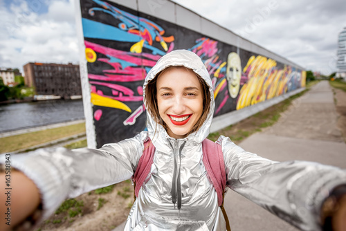 Foto op Plexiglas Graffiti Young woman tourist making selfie photo standing in front of the Berlin wall in Germany