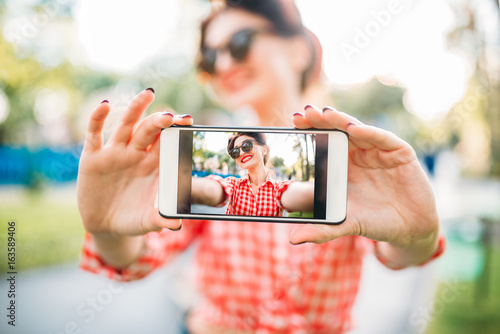 Plakát Pinup girl shows on phone outdoors selfie