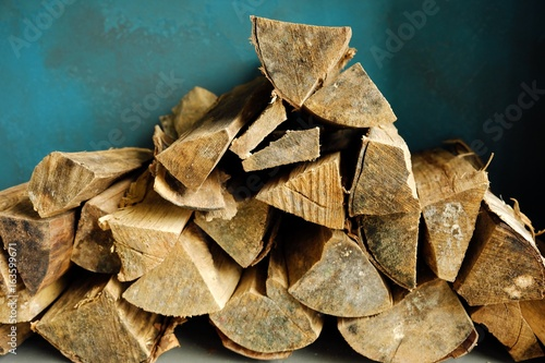 Brown firewood for the fireplace on a blue background