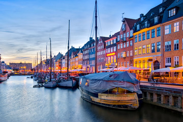 Nyhavn with its picturesque harbor with old sailing ships and colorful facades of old houses in Copenhagen, Denmark