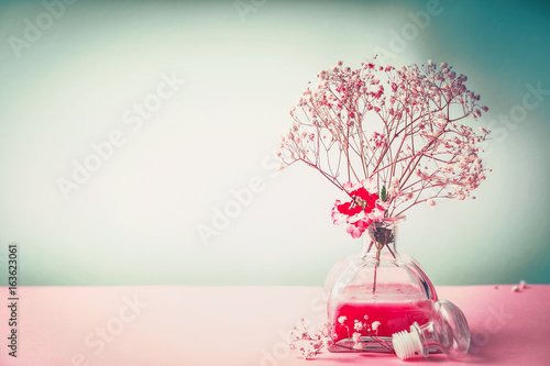 Spa , wellness or natural cosmetic still life with bottle of lotion and flowers on pastel color background, front view, banner, beauty concept