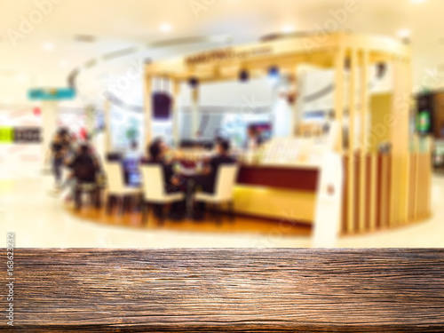 Abstract blur and defocused restaurant in shopping mall department and retail store interior for background and empty wooden table space platform for present product.
