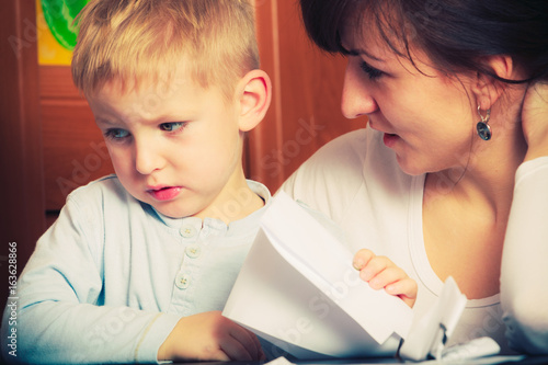 Kid playing with mother, drawing pictures on paper