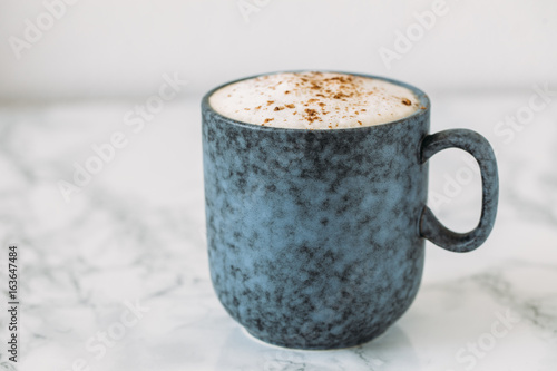 Tuinposter Chocolade Cappuccino in a rustic style mug on a marble table