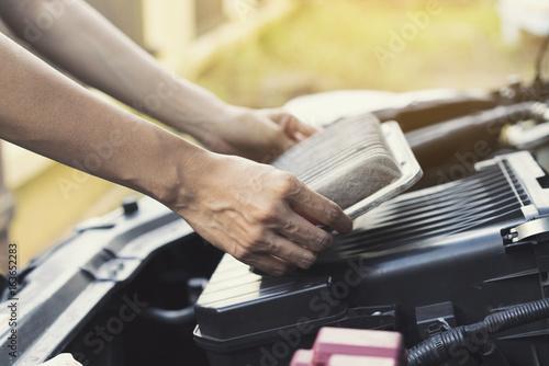 fototapeta na ścianę Technician holding dirty air filter for car, maintenance and repair concept