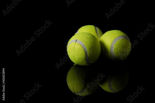 Staande foto Stierenvechten Three tennis balls isolated on a black background