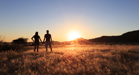 Couple at african savanna landscape. Namibia, South of Africa.