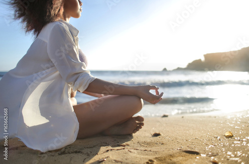Papiers peints Ecole de Yoga Beautiful girl relaxing and doing yoga at the beach
