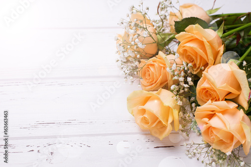 Fresh peach color roses flowers on white wooden background in ray of light .