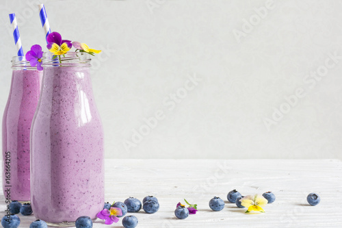 Foto op Plexiglas Milkshake blueberry smoothie or milkshake in bottles with flowers and straw