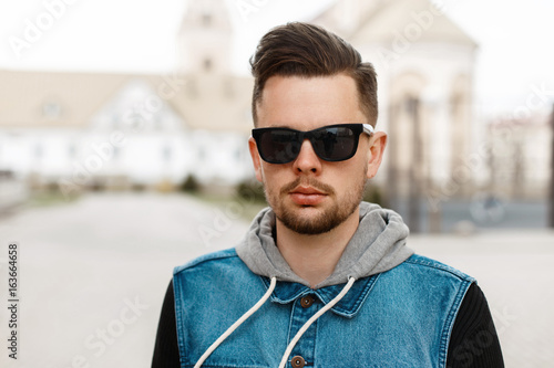 Portrait of a handsome guy in sunglasses and a denim jacket in the city