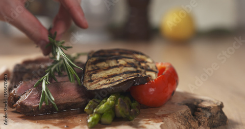 serving medium rib eye steak with rosemary