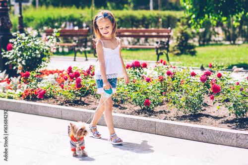 Little girl is walking with a dog in the park