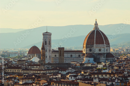 Elevated view of Santa Maria Del Fiore cathedral with mountains in the background at sunset