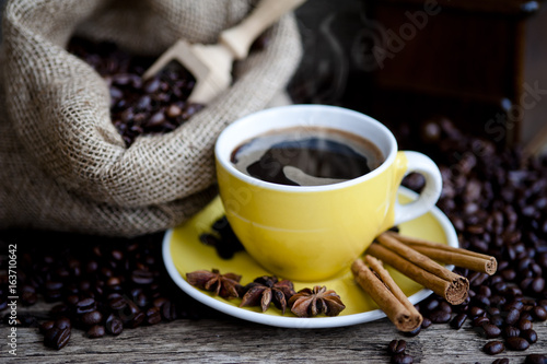 A cup of coffee and coffee beans on a wooden table