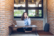 Portrait of young mixed race businesswoman (Her dad is British, Her mom is Thailand) speaking on her mobile phone and sitting in modern interior office.