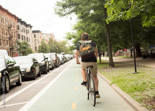 Back view of young hipster caucasian man riding bike on bike lane