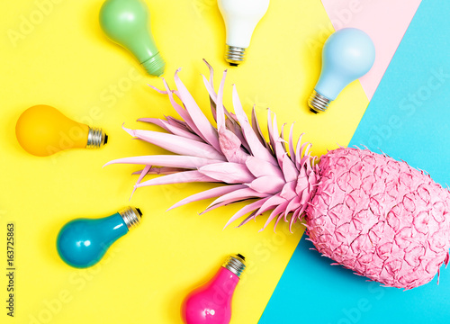 Painted pineapple with light bulbs on bright colored paper background - 163725863