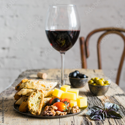 Glass of red wine and snacks on wooden table