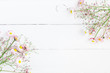 Flowers composition. Frame made of pink gypsophila flowers and daisy flowers on white wooden background. Flat lay, top view, copy space
